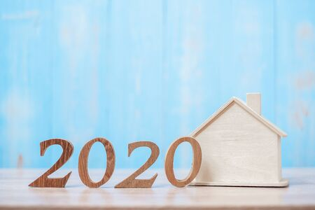 2020 number with house model on wooden background. Banking, real estate, investment, financial, savings and New Year Resolution concepts