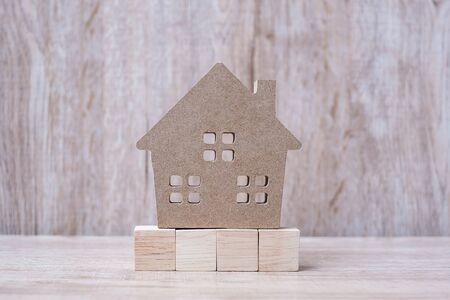 Wood block and house model on wooden background. Banking, real estate, Property investment, home mortgage, financial and savings concepts Stockfoto
