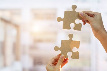 Woman hands connecting couple puzzle piece against sunrise effect, businesswoman holding wood jigsaw with sunset background. Business solutions, target, success, goals and strategy concepts Banque d'images