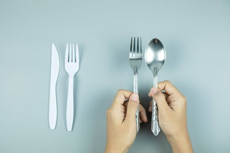 Man holding Stainless Steel spoon and fork over white plastic tool. Environmental Protection, Zero waste, Reusable, Say No Plastic, World Environment day and Earth day concept
