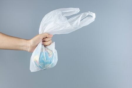 Man holding plastic bag and Globe inside against gray background with Copy space for text. Environmental Protection, Zero waste, Reusable, Say No Plastic, World Environment day and Earth day concept Reklamní fotografie