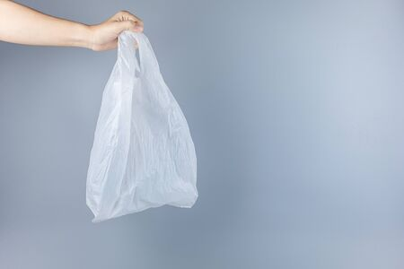 Man holding plastic bag against gray background with Copy space for text. Environmental Protection, Zero waste, Reusable, Say No Plastic, World Environment day and Earth day concept