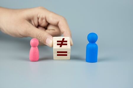 Hand change cube block of unequal to a equal sign between Pink Women and Blue Men wooden symbol. gender equality concept Stok Fotoğraf