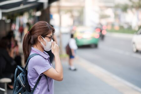 young Asian woman wearing N95 respiratory mask protect and filter pm2.5 (particulate matter) against traffic and dust city. healthcare and air pollution concept