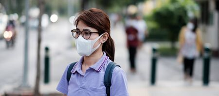 young Asian woman wearing protection mask against flu virus in the city. healthcare and air pollution concept Stok Fotoğraf
