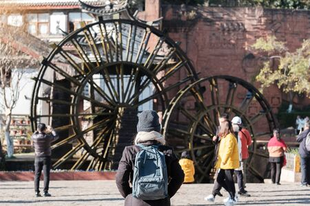 young woman traveler traveling at Giant Water Wheels in Lijiang Old Town, landmark and popular spot for tourists attractions in Lijiang, Yunnan, China. Asia travel concept