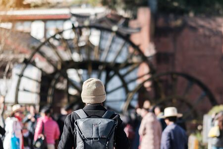 young man traveler traveling at Giant Water Wheels in Lijiang Old Town, landmark and popular spot for tourists attractions in Lijiang, Yunnan, China. Asia travel concept Stok Fotoğraf
