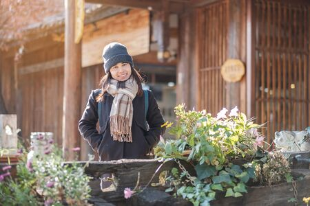 Happy young woman traveler traveling at the Square street in Lijiang Old Town, landmark and popular spot for tourists attractions in Lijiang, Yunnan, China. Asia travel concept
