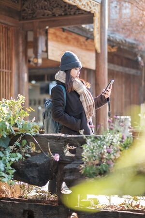 Happy young woman traveler using mobile phone or shelfie photography at Lijiang Old Town, landmark for tourist attractions in Lijiang, Yunnan, China. Asia travel concept