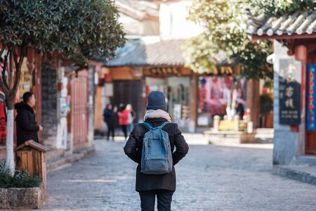 young woman traveler traveling at the Square street in Lijiang Old Town, landmark and popular spot for tourists attractions in Lijiang, Yunnan, China. Asia travel concept