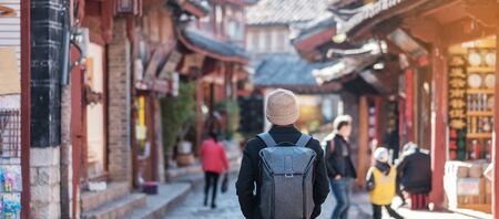 young man traveler traveling at the Square street in Lijiang Old Town, landmark and popular spot for tourists attractions in Lijiang, Yunnan, China. Asia travel concept Stok Fotoğraf