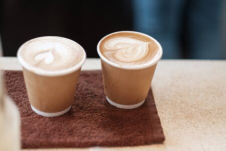 Couple Hot coffee paper cup, heart shape latte coffee art. Love, holiday, Valentine day and free plastic container concept