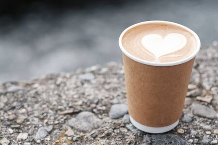 Hot coffee paper cup against river background, heart shape latte coffee art. Love, holiday, Valentine day and free plastic container concept