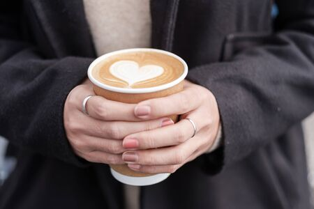 Woman hands holding Hot coffee paper cup, heart shape latte coffee art. Love, holiday, Valentine day and free plastic container concept
