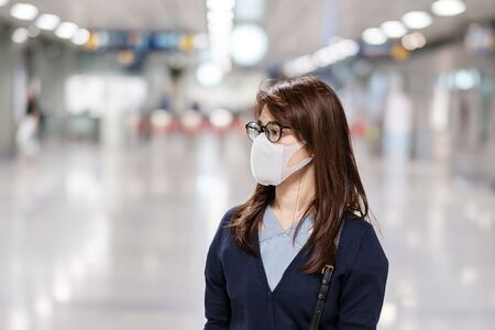 young Asian woman wearing protection mask against Novel coronavirus or Corona Virus Disease (Covid-19) at airport, is a contagious virus that causes respiratory infection.Healthcare concept Stock Photo