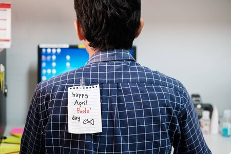 Back of young man office with a white paper note attached with the text happy april fools day Фото со стока