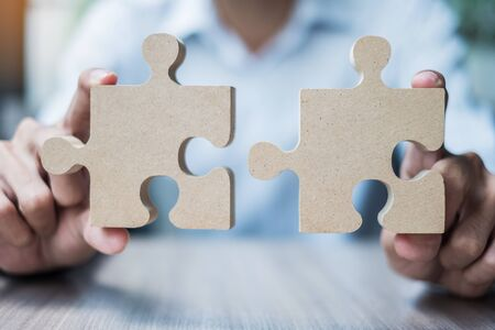 man hands connecting couple puzzle over table, businessman holding wood jigsaw inside office. Business solutions, mission, target, success, goals and strategy concepts Banque d'images
