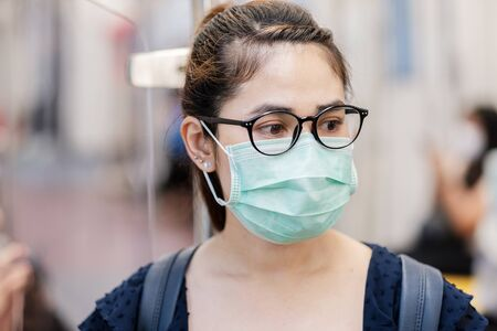 young Asian woman wearing Surgical face mask against Novel coronavirus or Corona Virus Disease (Covid-19) at public subway train. Hygiene, Healthcare and infection concept