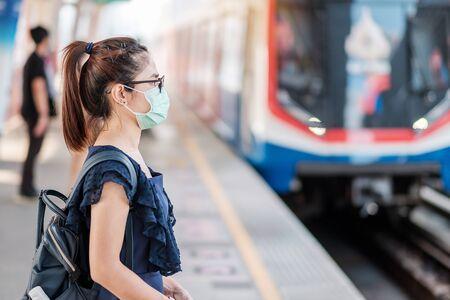 亚洲年轻女性在公共火车站佩戴外科口罩,以预防新型冠状病毒或冠状病毒病(Covid-19)。卫生、保健和感染概念