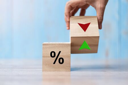 business man Hand change wood cube block with percentage to UP and Down arrow symbol icon. Interest rate, stocks, financial, ranking, mortgage rates and Cut loss concept