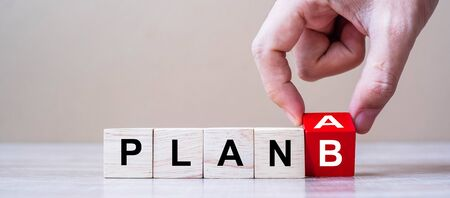 Businessman hand flipping wooden cube blocks with PLAN A change to PLAN B text on table background. strategy, analysis, marketing, project and Crisis concepts