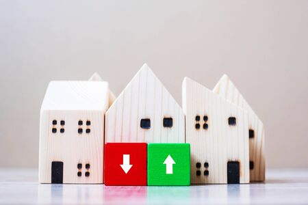 Financial cube blocks with wooden house model on table background. Crisis, fall Business, Risk, Economic recession, Developer, Real Estate and Property concept