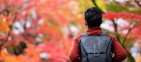 Happy man tourist looking colorful leaves in the garden, young Asian traveler visit in Kyoto city, Japan and enjoying with beautiful nature in Autumn season. Vacation, Sightseeing and travel concept Stock Photo