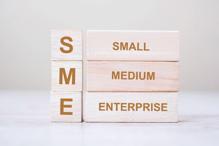 SME text (Small Medium Enterprise) wooden cube blocks on table background. Financial, Investment, marketing, startup and business concepts