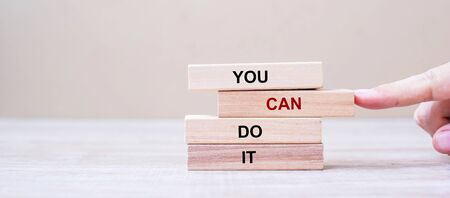 YOU CAN DO IT wooden blocks on table background, Businessman hand placing or pulling wooden block with CAN word on the tower. Business and Attitude Positive Concepts