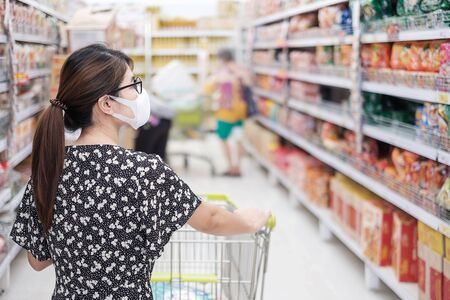 Asian woman wearing protective mask and  shopping in supermarket or grocery, protect coronavirus inflection. social distancing, new normal and life after covid-19 pandemic