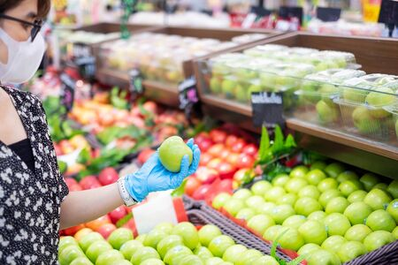 Asian woman wearing nitrile gloves and holding green apple fruit in supermarket or grocery, protect coronavirus inflection. Hygiene, new normal and life after covid-19 pandemic Imagens