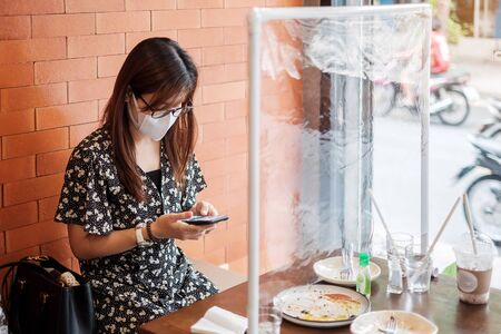 Asian woman using smartphone during dining time in restaurant with separated of shield plastic partition, protect coronavirus inflection. social distancing, new normal and life after covid-19 pandemic