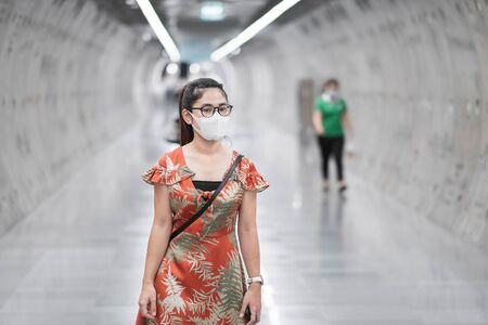 young Asian girl wearing Surgical face mask protect coronavirus inflection, Happy tourist woman walking in public subway station. social distancing, new normal and life after covid-19 pandemic