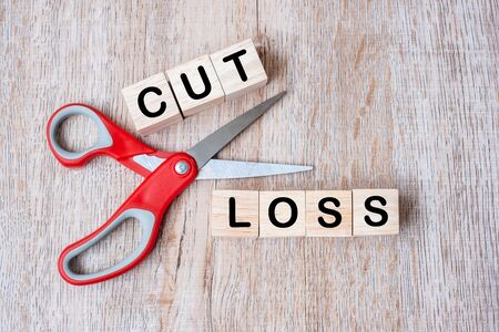 Cut Loss wooden cube blocks and Scissors on table background. Stock market, crisis, economic depression and risk businesses concepts