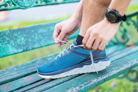 Young adult male in sportswear and smartwatch tying shoelace in the park outdoor, athlete runner man ready for running and jogging in morning. Exercise, wellness, healthy lifestyle and workout concept
