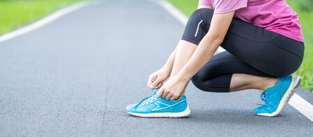 Young adult female in sportswear tying shoelace in the park outdoor, athlete runner woman ready for running and jogging in morning. Exercise, wellness, healthy lifestyle and workout concept