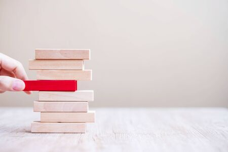 Businessman hand placing or pulling red wooden block on the tower. Business planning, risk Management, Solution, Resolving and strategy Concepts