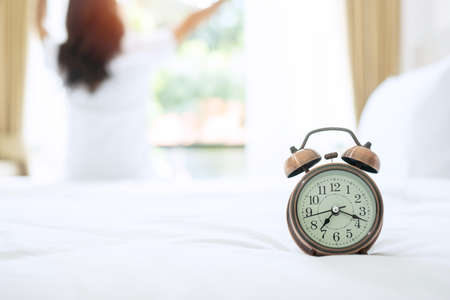 Retro alarm clock on bed in the morning sunlight, wake up, fresh relax, have a nice day and daily routine concept Фото со стока
