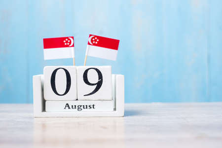 Wooden calendar of August 9th with miniature Singapore flags. Singapore's independence day, city-state National Day and happy celebration republic concepts