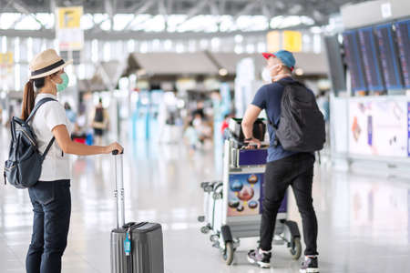 Young female wearing face mask with luggage checking flight time in airport, protection Coronavirus disease (Covid-19) infection, Asian woman traveler with hat. New Normal and travel bubble concept