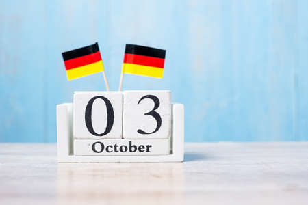 Wooden calendar of October 3rd with miniature Germany flags. German Unity Day and happy celebration concepts