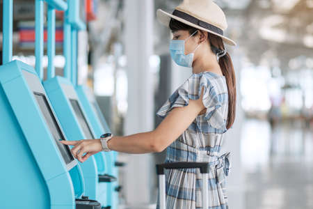 woman wearing medical face mask and using the self check-in machine at the airport terminal getting the boarding pass, Asian woman traveler ready to travel. New Normal and safety travel under COVID-19