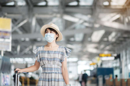Young female wearing face mask with luggage checking flight time in airport, protection Coronavirus disease infection, Asian woman traveler ready to travel. New Normal and travel under COVID-19 Reklamní fotografie