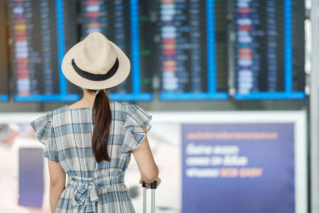 Young woman traveler checking flight time, Asian passenger with hat looking to information board in international airport terminal. Travel, trip, summer vacation and world tourism day concept