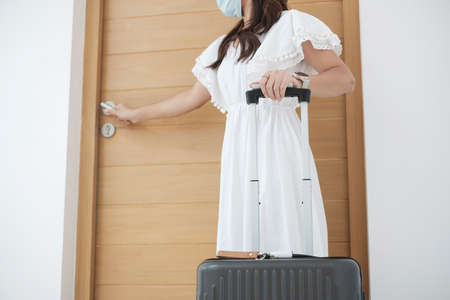Happy tourist woman wearing surgical face mask and open door, young female in white dress enjoy traveling at tropical hotel. New Normal, summer,  travel under Covid-19, vacation and holiday concept Reklamní fotografie