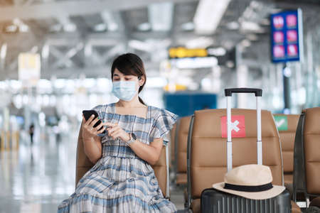 Young female wearing face mask and using mobile smartphone in airport, protection Coronavirus disease (Covid-19) infection, Asian woman traveler sitting on chair. New Normal and social distancing Standard-Bild