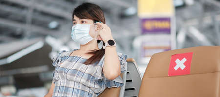 Young female wearing face mask in airport terminal, protection Coronavirus disease (Covid-19) infection, Asian woman traveler sitting on chair. New Normal, social distancing and safety travel concept