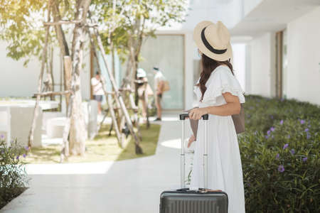 Happy tourist woman wearing surgical face mask protection Covid-19 infection, young female in white dress enjoy traveling at tropical hotel. New Normal, summer travel, vacation and holiday concept