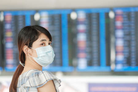Young female wearing surgical face mask checking flight time in airport, protection Coronavirus disease infection, Asian woman traveler ready to travel. New Normal and safety travel under COVID-19