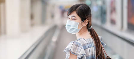 Young adult female wearing face mask in airport terminal, protection Coronavirus disease infection, Asian woman traveler walking on escalator in aerodrome. New Normal and travel under COVID-19 concept